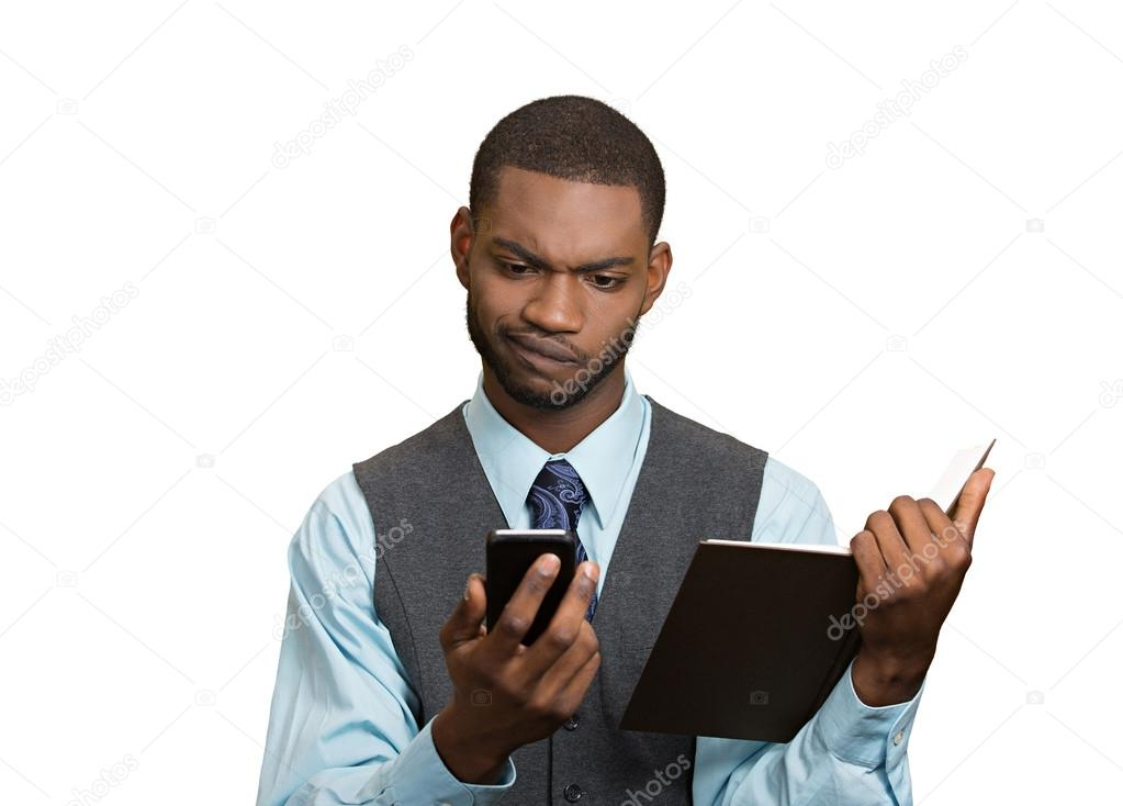 Skeptical man looking at phone holding book
