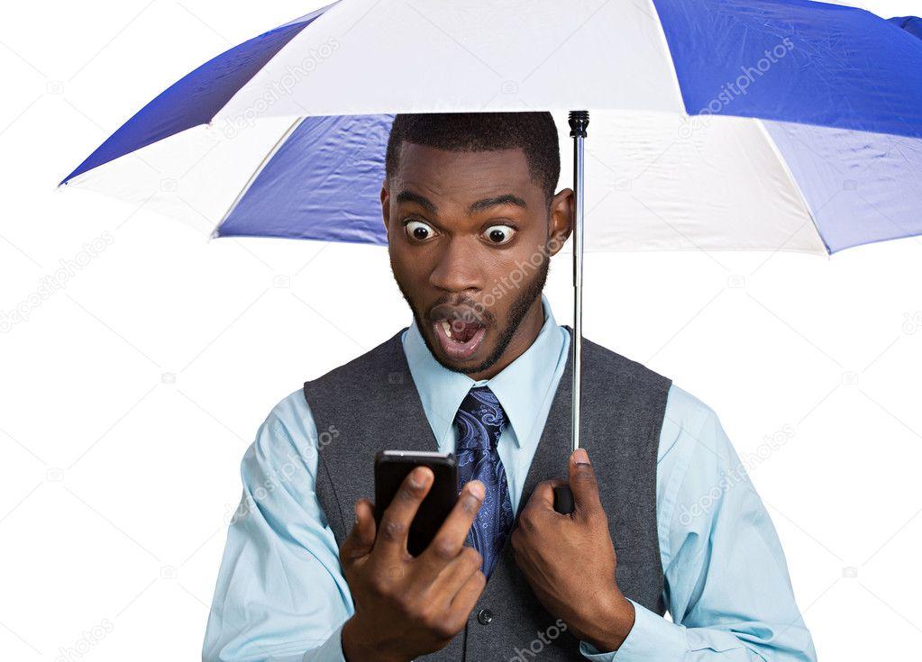 Man reading news on phone holding umbrella