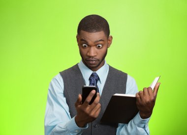 Shoked man with phone holding book