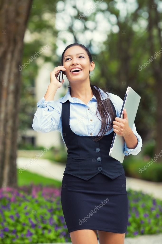 Happy busy business woman walking while talking on a smart phone