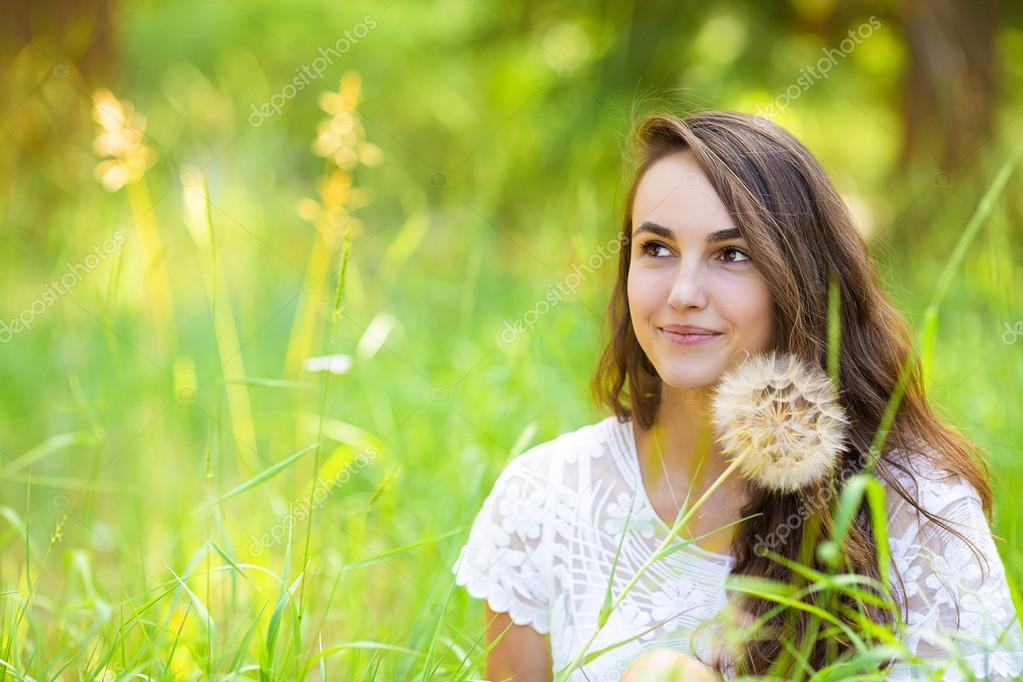 Happy young beautiful woman sitting on grass with dandelion flow