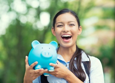 Happy woman holding piggy bank