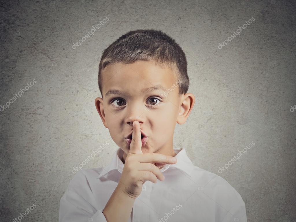 Boy placing finger on lips, quiet gesture