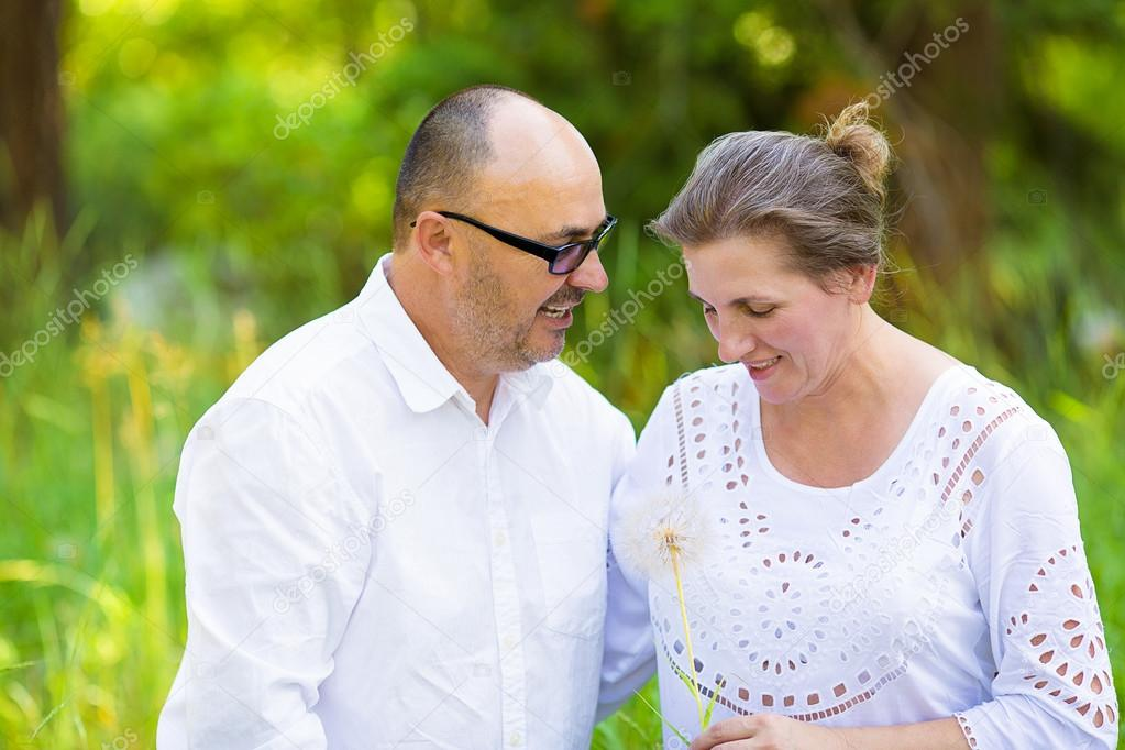 Happy mature couple enjoying weekend day in a park