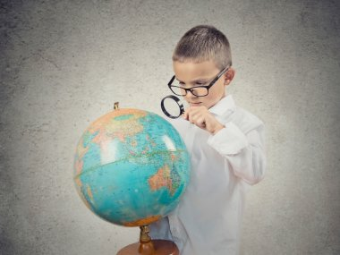 Boy looking through magnifying loupe on globe map