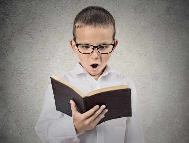 Surprised boy reading book