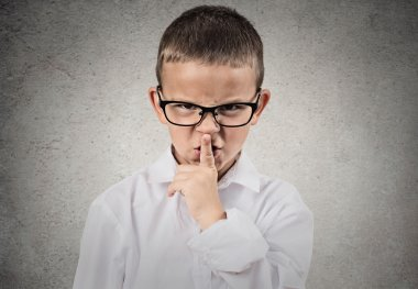 Boy giving be quiet gesture with finger on lips