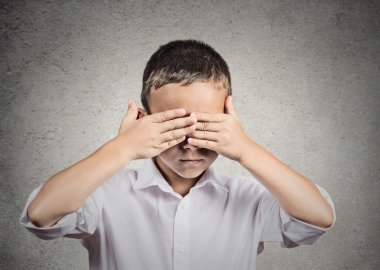 Boy covers his eyes with hands. Hear no evil concept