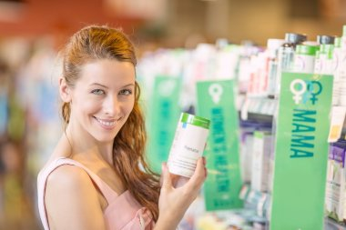 Happy woman picking daily food supplements in a store