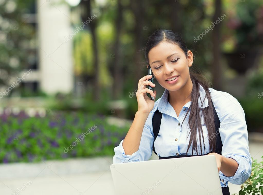 Woman talking on a phone, looking on laptop screen