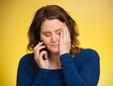 Sad stressed hopeless woman talking on a mobile phone