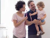Fotografie Mutter und Vater lehren ihre Tochter die Zähne zu putzen