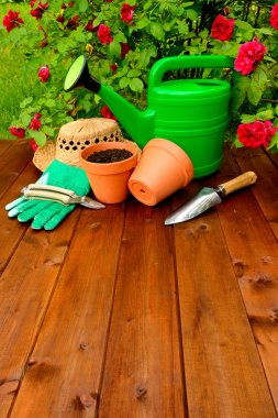 Gardening tools on wooden table and rose flowers background
