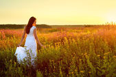 Fotografie Young woman in white clothes standing in field on sunset