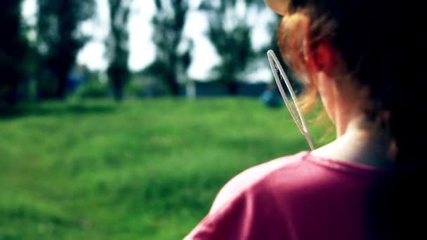 Červené roztomilá dívka fouká soapbubbles