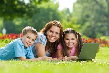 Happy Family using laptop lying on grass