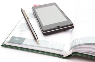 Modern mobile phone and pen lying on open calendar
