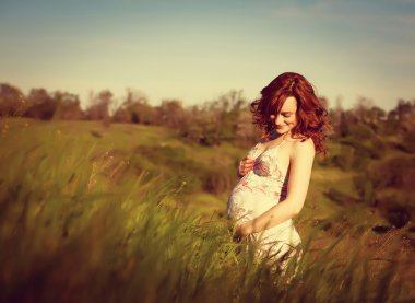 Young happy pregnant woman relaxing and enjoying life in nature.