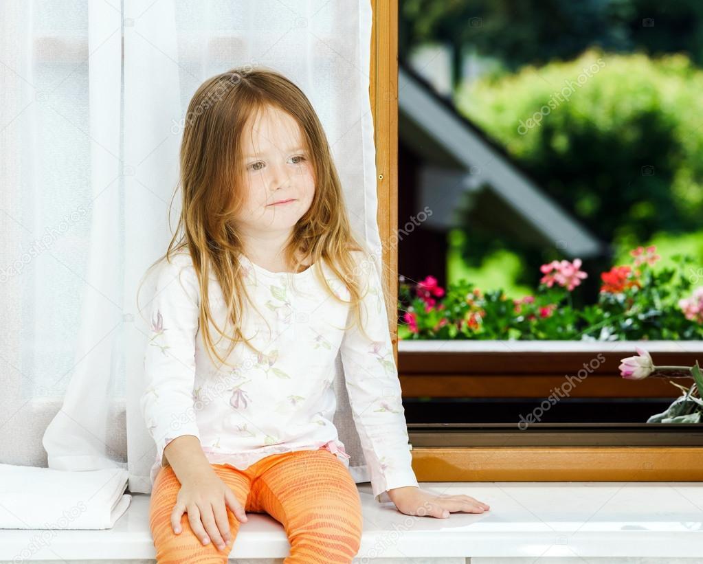 Entzückendes kleines Mädchen im blühenden Apfelbaum