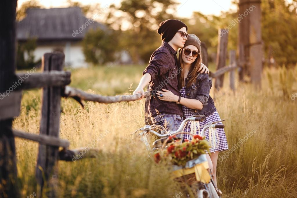 Two beautiful hipsters standing outdoor in summer with white vintage fixed gear bicycle