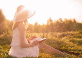 Girl in dress reading book.