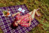Hintergrund-Mädchen, die im Sommer zu ihrem Ful auf Plaid auf dem Gras liegend