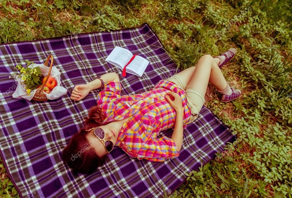 Background girl lying on plaid on the grass in summer to her ful