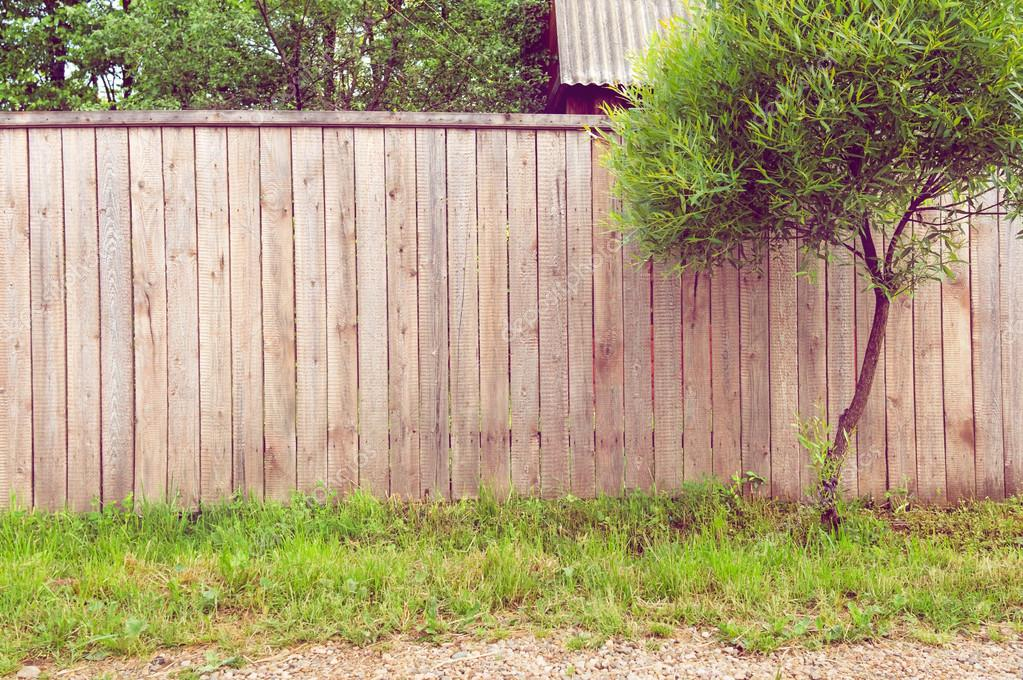 Background rustic wooden fence with green grass, road and tree