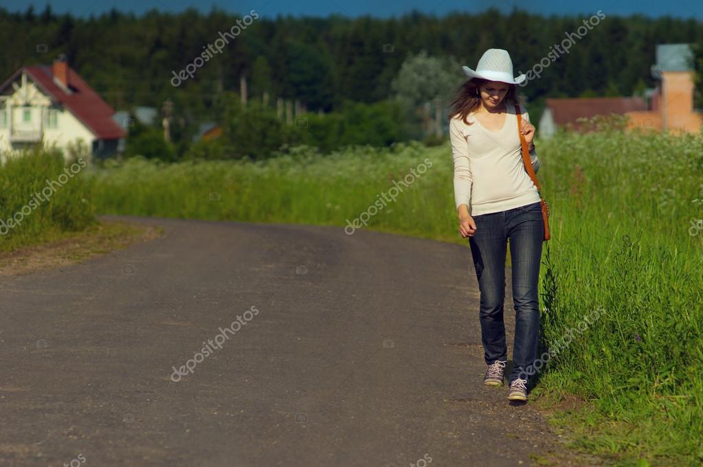 Fondo chica va bien por la carretera de campo en un sombrero de vaquero y  una bolsa en las manos 5775e768f2c