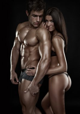 sexy couple, beautiful woman holding a muscular man isolated on