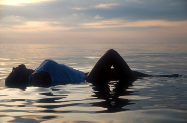 Swimwear Model in Sexy Bikini - one outstanding model - travel the world and relax and restore energy seaside - ocean walks stroll on the Pacific Ocean in Lima Peru  sunrise sunset breasts and legs above the water line ripples shadow