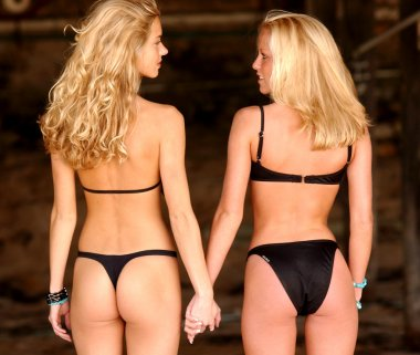Best Friends - Double Blondes  - Double Bikinis holding hands looking at each other admiring each other stunning standing slim hour glass shape