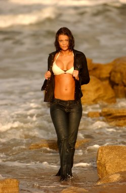 Playboy Model Vanessa Wolfson Wet Blue Jean Jacket and Pants walking on beach sand ocean waves rock background open top showing white bikini top stunning standing slim hour glass shape natural perky look of real suggestive provocative beauty