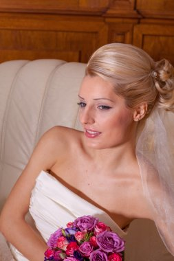 Indoor portrait of adorable bride with blonde hair sitting on a sofa.