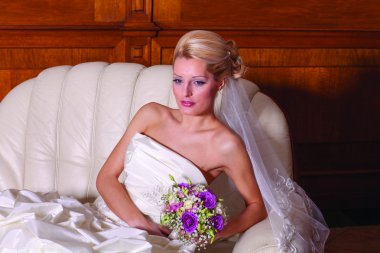 Indoor close up portrait of charming bride with blonde hair sitting on a sofa.