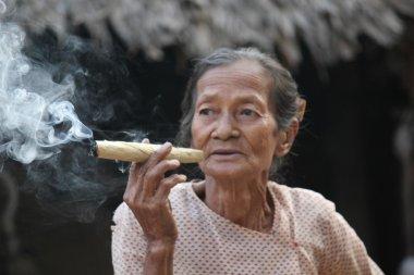 Asiatic woman smoking an handmade cigar