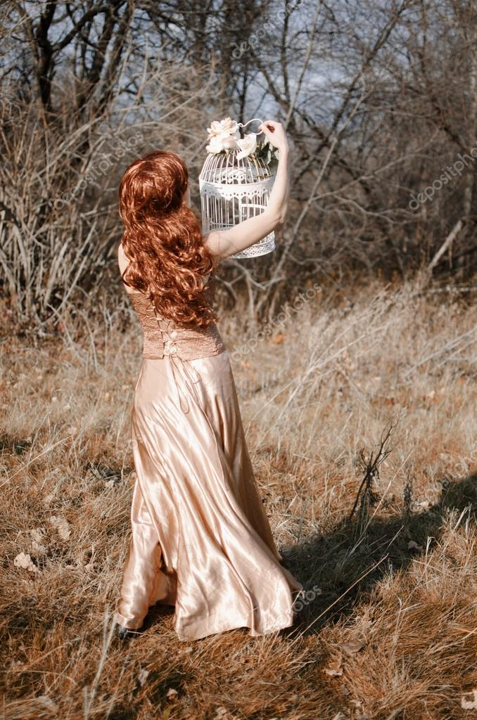 Redhead girl with bird cage