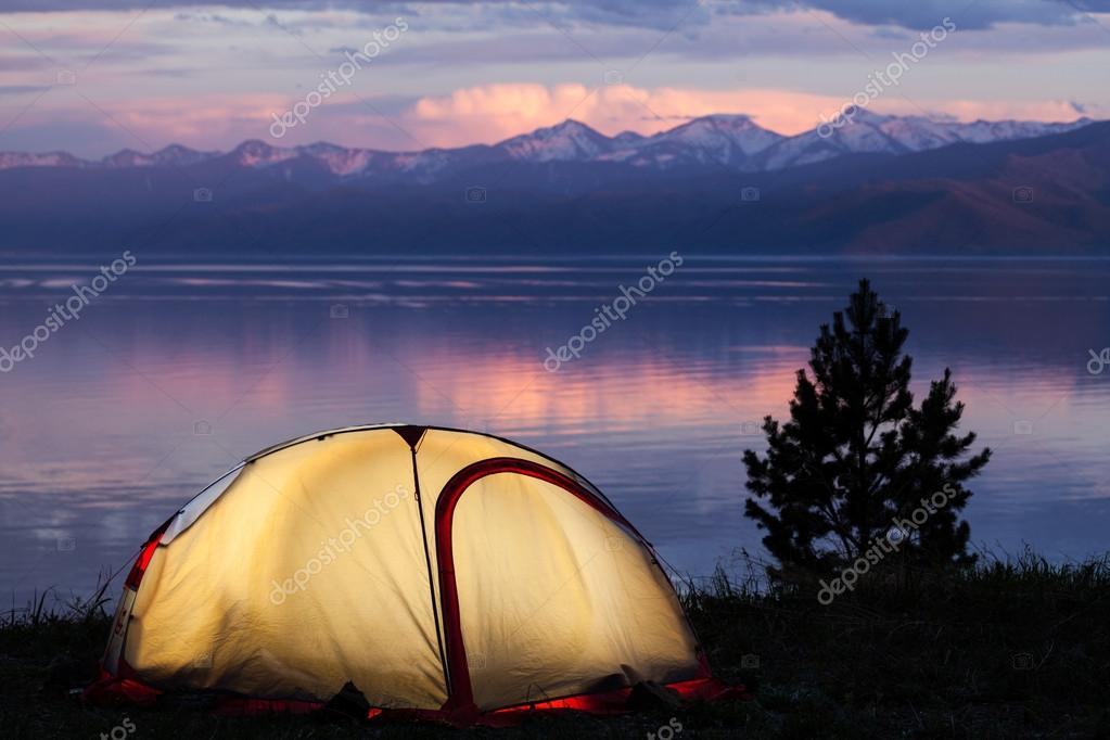 Tent across beautiful sunset on lake