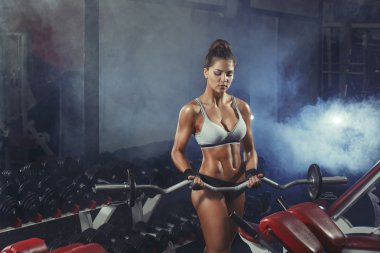 Young sexy woman training with barbell in the gym on smoke backg