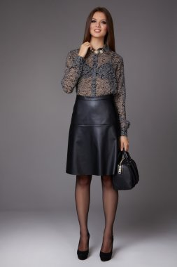 Beautiful business woman with evening make-up wearing a skirt to the knee a silk blouse with lace long sleeves and high-heeled shoes and a small black handbag, business clothes for meetings and walks