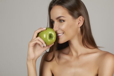 Young beautiful sexy girl with dark hair, bare shoulders and neck, holding big green apple to enjoy the taste and are dieting, healthy eating and organic foods, feeling temptation, hair shampoo