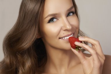 Beatiful girl with Perfect smile eat red strawberry. white teeth