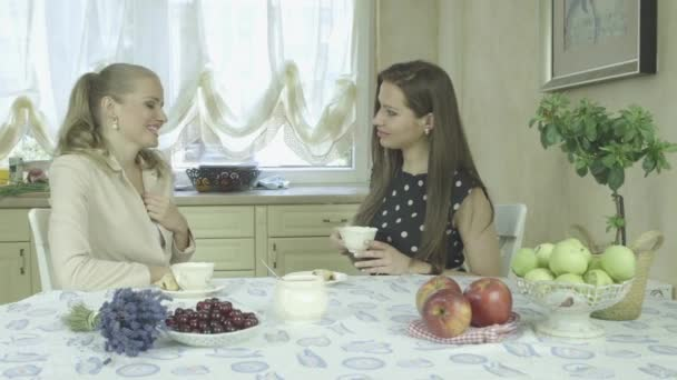 Two attractive happy young women having fun at dining table