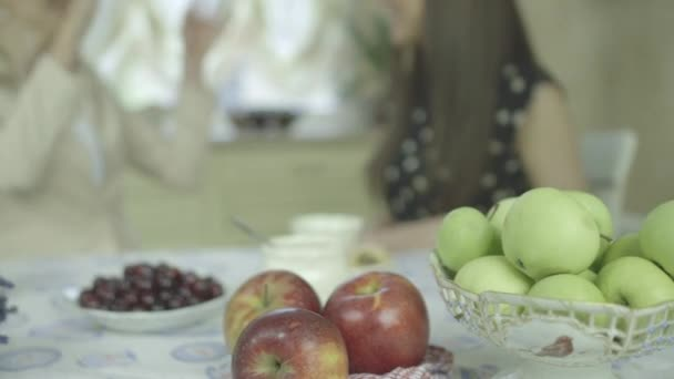 Fruits on the table and two chatting women on the background