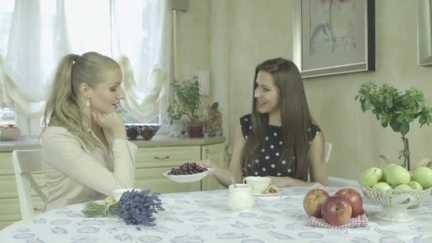 két elegáns vonzó mosolygó fiatal nő étkezőasztal kávé idő, amelynek