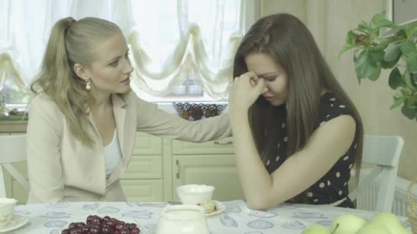 mladá žena uklidňující smutný přítel v kuchyni