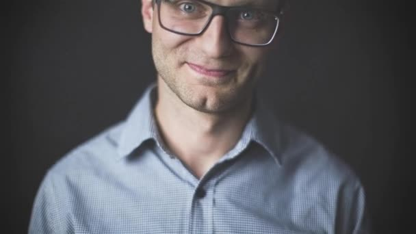 Portrait of young attractive man with glasses smiling  over black background