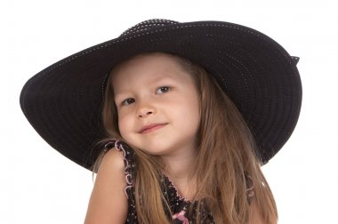 Cute smiling girl at the age of five in big black hat