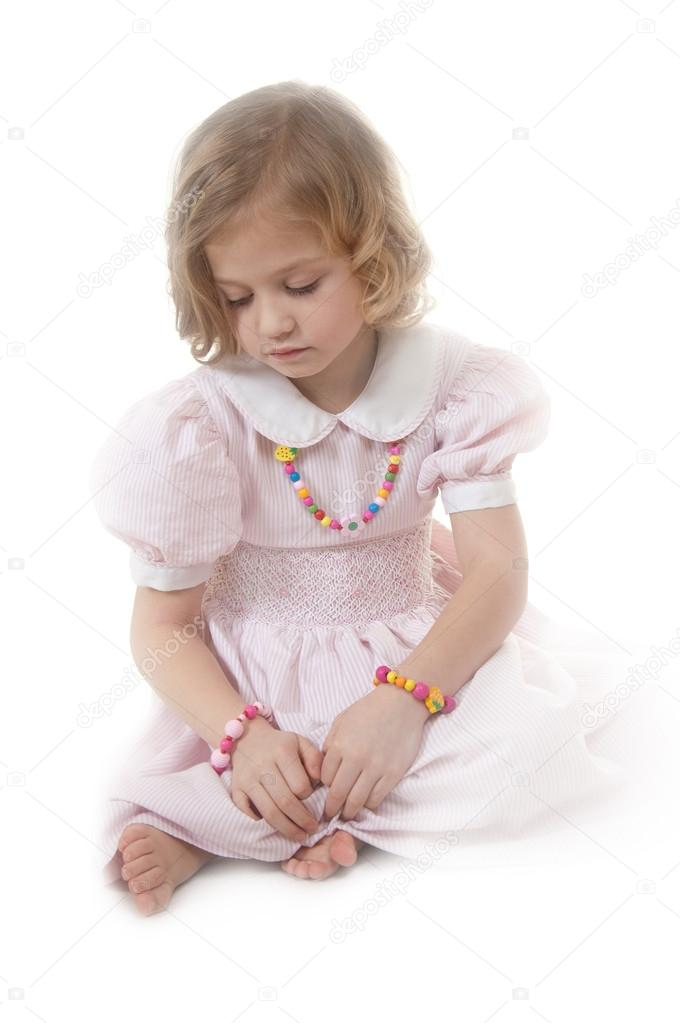 12c47b69acea Sad adorable little girl at the age of five wearing a pink dress looking  down thoughtfully on white background — Photo by ...
