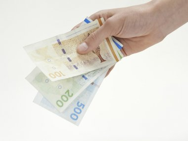 A hand holding Danish currency